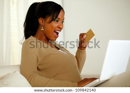 Portrait of a charming young woman holding a gold credit card while buying on the Internet with her laptop at home indoor - stock photo