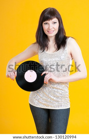 Portrait of a charming young woman holding a vinyl record - stock photo