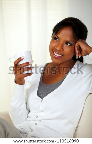 Portrait of a charming young woman holding a white mug while sitting pensive on couch at home indoor