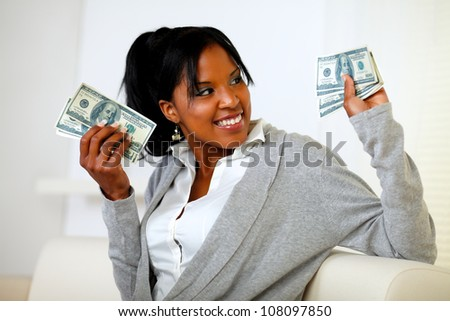 Portrait of a charming young woman holding plenty of cash money while is looking to his left - stock photo