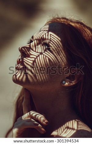 Portrait of a charming young woman outdoor. Light and shadow. interesting portrait of young girl's face covered with unusual shadow - stock photo