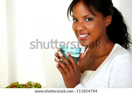 Portrait of a charming young woman smiling and drinking fresh water while looking at you - stock photo