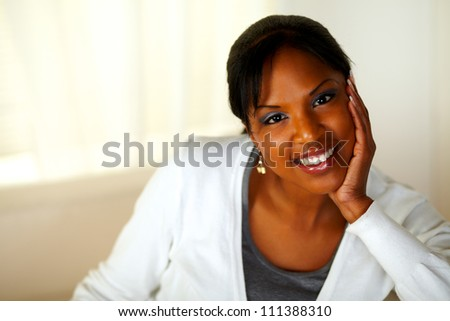 Portrait of a charming young woman smiling and looking at you while sitting on couch. With Copyspace