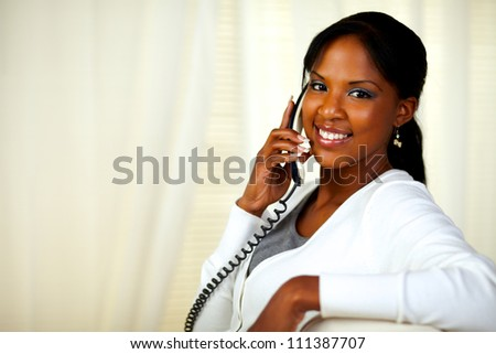 Portrait of a charming young woman smiling at you while conversing on phone. With copyspace