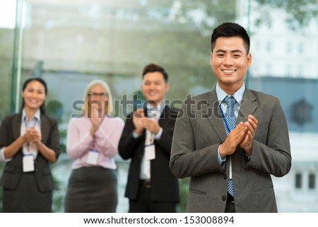Portrait of a cheerful applauding businessman on the foreground - stock photo