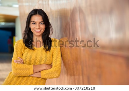 Portrait of a cheerful attractive businesswoman standing with arms folded in office - stock photo