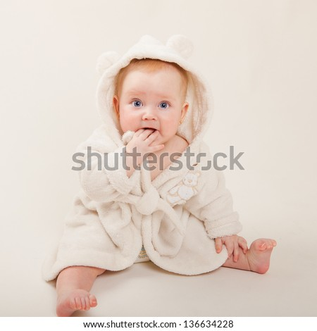 Portrait of a cheerful baby girl with blue eyes in white bathrobe, isolated over white - stock photo