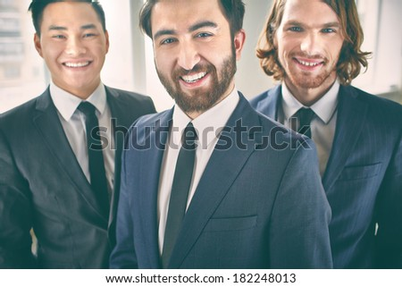 Portrait of a cheerful beaded businessman posing with his colleagues on the foreground