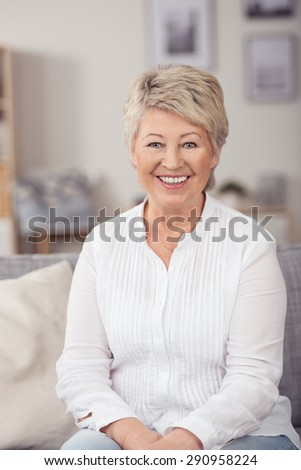 Portrait of a Cheerful Blond Middle Aged Woman Sitting at the Sofa in the Living Room, Looking at Camera with a Toothy Smile. - stock photo
