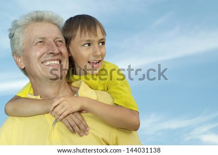Portrait of a cheerful boy and his grandfather on a sky background - stock photo