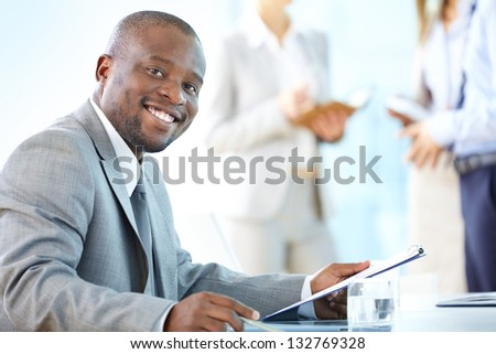 Portrait of a cheerful business worker smiling at the camera - stock photo