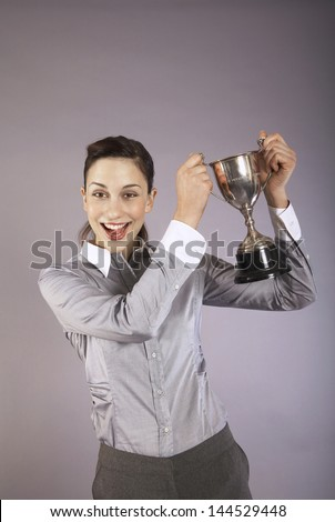 Portrait of a cheerful businesswoman holding up trophy against purple background - stock photo
