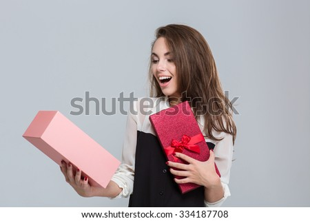 Portrait of a cheerful businesswoman opening gift box over gray background - stock photo
