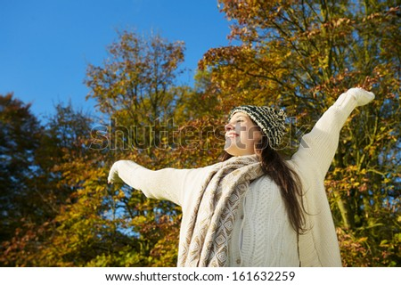 Portrait of a cheerful, carefree woman enjoying sunny autumn day with arms outstretched