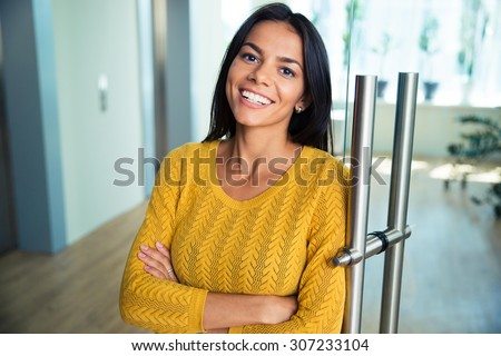 Portrait of a cheerful casual businesswoman standing with arms folded in office - stock photo