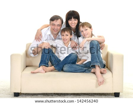 Portrait of a cheerful Caucasian family of four on a light background