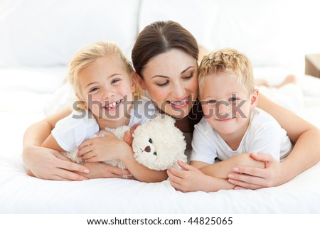 Portrait of a cheerful children with their mother lying on a bed