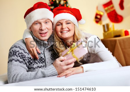 Portrait of a cheerful Christmas couple, man holding a gift-box - stock photo