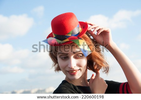 portrait of a cheerful clown with the red hat on the background of blue sky - stock photo