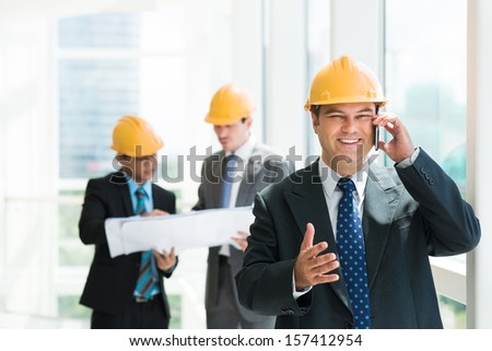 Portrait of a cheerful construction worker talking by phone and looking at camera on the foreground - stock photo