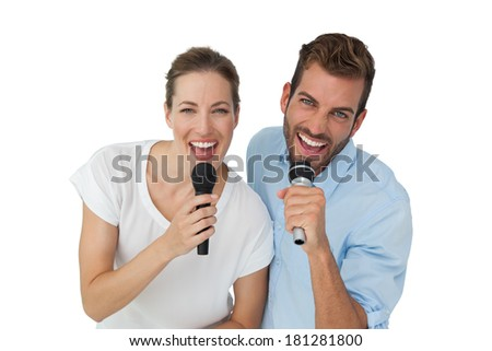 Portrait of a cheerful couple singing into microphones over white background - stock photo