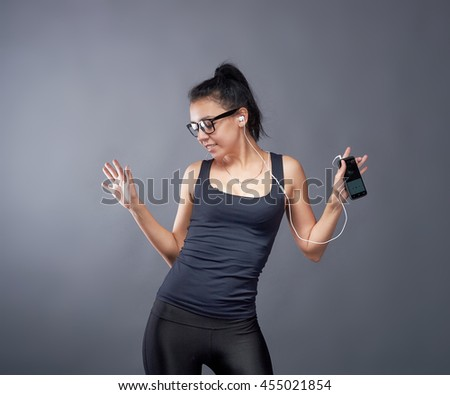 Portrait of a cheerful cute woman brunette in sportswear listening music in headphones and dancing isolated on a grey background - stock photo