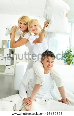 Portrait of a cheerful family fighting pillows, father carrying his daughter on shoulders - stock photo