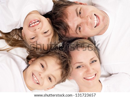 Portrait of a cheerful family having fun together lying on a bed at home - top view