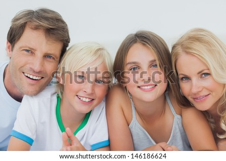 Portrait of a cheerful family lying on the bed - stock photo