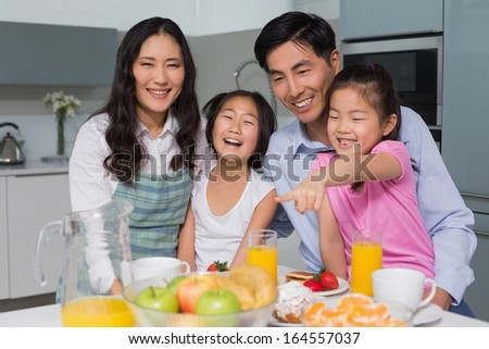 Portrait of a cheerful family of four enjoying healthy breakfast in the kitchen at home