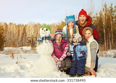portrait of a cheerful family with snowman. happy children and parents in the winter outdoors - stock photo