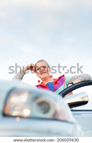 Portrait of a cheerful female teen driver, by her new car, looking very happy - stock photo