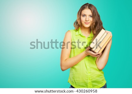 Portrait of a cheerful female teenager with a  book - stock photo