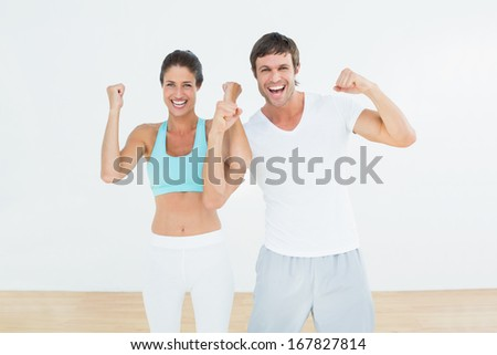 Portrait of a cheerful fit young couple clenching fists in the fitness studio - stock photo
