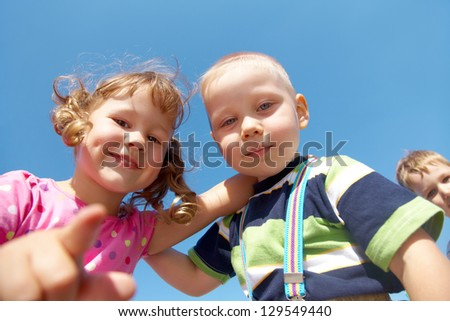 Portrait of a cheerful girl and boy blue sky background - stock photo