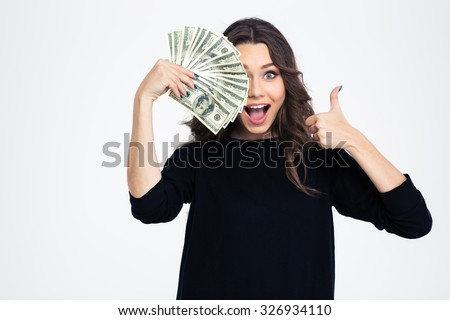 Portrait of a cheerful girl covering her eye with dollar bills and showing thumb up isolated on a white background - stock photo