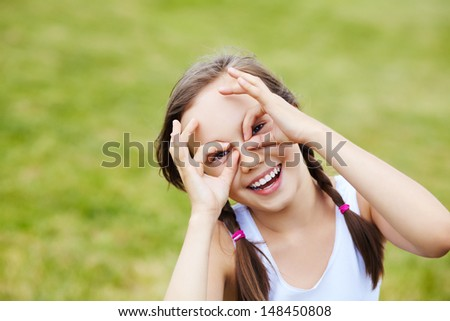 portrait of a cheerful girl who portrays glasses hands, over green background - stock photo