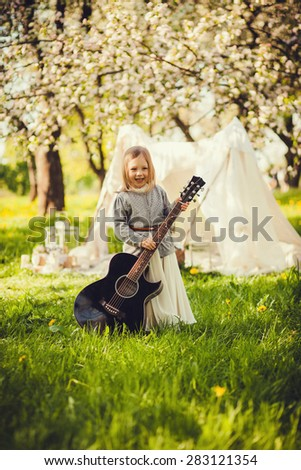 Portrait of a cheerful girl with a guitar outdoors. fun game guitar - stock photo
