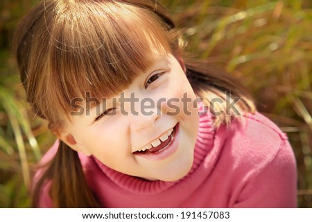 Portrait of a cheerful happy cute winking girl closeup
