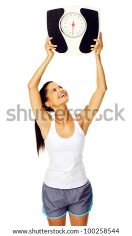 portrait of a cheerful hispanic woman who is happy with her weight and holds scale above her head - stock photo