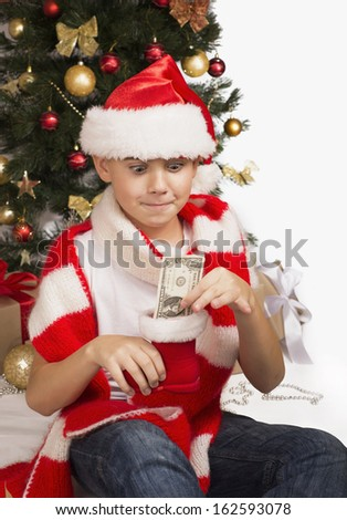 Portrait of a cheerful little boy holding a dollars - stock photo