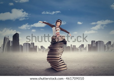 Portrait of a cheerful little boy sitting on a pile of books while wearing helmet