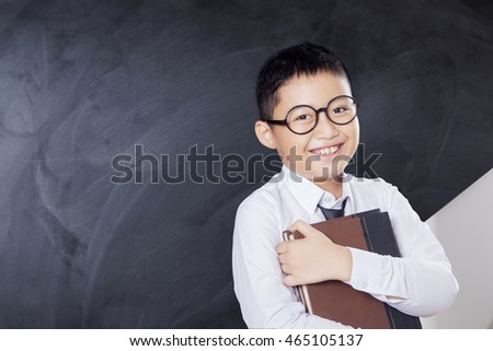 Portrait of a cheerful little boy standing in the classroom while wearing glasses and holding a book in front of blackboard