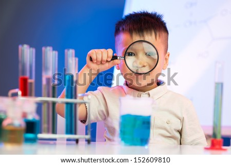 Portrait of a cheerful little boy with a magnifier in the lab on the foreground