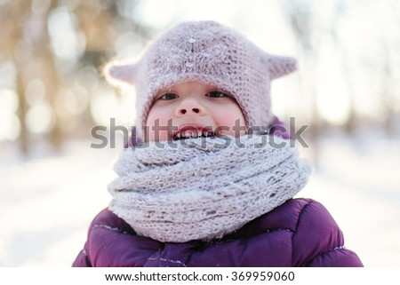 Portrait of a cheerful little girl during a winter walk in the woods. Focus on the scarf - stock photo