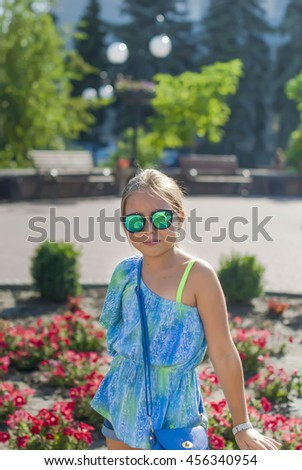 portrait of a cheerful little girl in glasses with a mischievous smile on the background of flowers and municipal buildings - stock photo