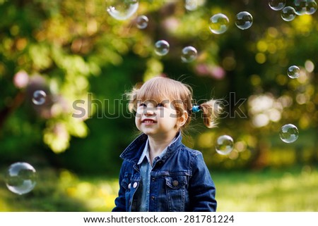 Portrait of a cheerful little girl with soap bubbles, outdoor - stock photo