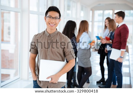 Portrait of a cheerful male student standing in university hall with classmates on background - stock photo