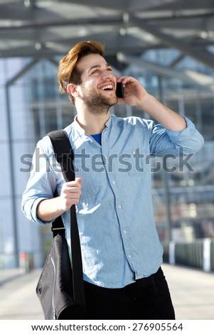 Portrait of a cheerful male traveler walking and talking on mobile phone  - stock photo