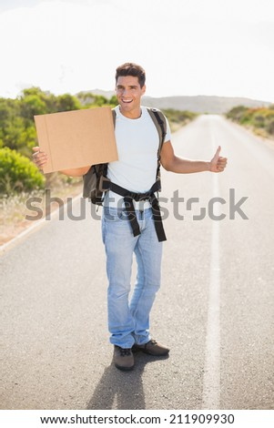 Portrait of a cheerful man hitchhiking with cardboard on countryside road - stock photo